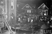 The crowd in Avers Avenue remains large well after the fire is out and most victims have been removed. Looking west in the alley between the school and Glowacki's candy store. (Life Magazine Photo)