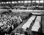 "The front rows nearest the coffins were reserved for the families of the 27 young victims whose coffins stretched before them. The Illinois National Guard Armory was chosen for the service because the church had no facilities large enough to accomodate the anticipated crowd. Nearly 7,000 mourners filled the building to capacity for the service. (Photo courtesy of Witold ""Vic"" Szmyd)"