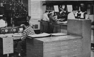 "This photo from 1960 shows Fire Main at city hall, the dispatch center where telephone calls, such as the call reporting the OLA fire, were received. Here, operators would answer the phones, and depending upon the type of call, dispatch an ambulance, fire companies, or whatever was appropriate. Box alarms were received and dispatched here as well. The information was sent, via a ""joker"" and P.A. speakers in the various fire houses, by the dispatcher in front of the microphone in the center of the picture. Part of an electric wall map of the city's fire and rescue companies is visible at the upper left. (Photo courtesy of Greg Boyle)"