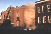 Smoke pours from the windows overlooking the small courtyard between the north and south wings of the school. When firemen arrived, there was a seven foot high iron picket fence blocking entrance to the courtyard. Firemen used valuable time breaking down the fence before they could begin rescue operations from room 211.