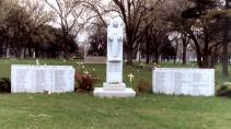 The memorial at Queen of Heaven cemetery, erected in 1960 by Monsignor Joseph Cussen. On either side of the statue of the Virgin Mary stand granite monuments engraved with the names of the three nuns and 92 children who died as a result of the Our Lady of the Angels fire. (Photo courtesy of Renee Jackson)