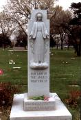"Our Lady of the Angels, the Virgin Mary, watches over the simple, flat grave markers of 25 of the students who died as a result of the school fire. The inscription at the base of the statue reads, ""In devout memory of the victims of the fire, December 1, 1958, at Our Lady of the Angels school. Erected by the Parishioners, the Priests, the Sisters and their Pastor, the Rt. Rev. Msgr. Joseph E. Cussen."" (Photo courtesy of Renee Jackson)"
