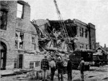 Several men watch demolition of the school from the alley on the north side of the school.